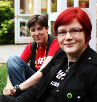 Two people sitting outdoors at BiCon Bisexuality Convention, smiling