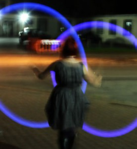 Back view of person at BiCon bisexuality convention swinging lighted poi at night