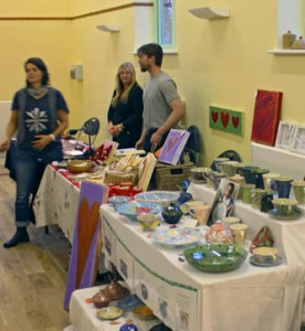 Two marketplace stalls selling art and pottery, with stallholders behind