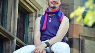 Person at BiCon bisexuality event sitting on top of a pillar, wearing bisexual colours and horns