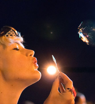 Person blowing bubbles at night at BiCon bisexuality convention